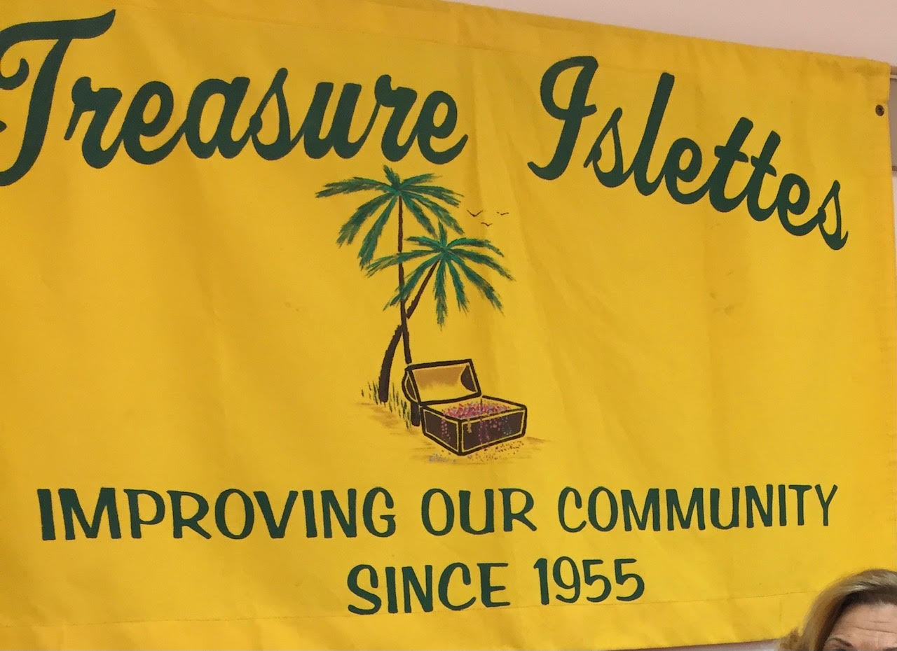 Yellow sign that reads Treasure Islettes in green with a logo of a palm tree