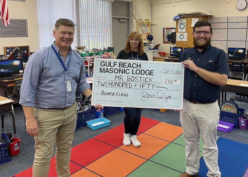 """A photo of two men standing in a school classroom holding a large check for $250 with the words """"Gulf Beach Masonic Lodge"""" and """"Mr. Bostock"""" written on it, with a woman standing in the background."""