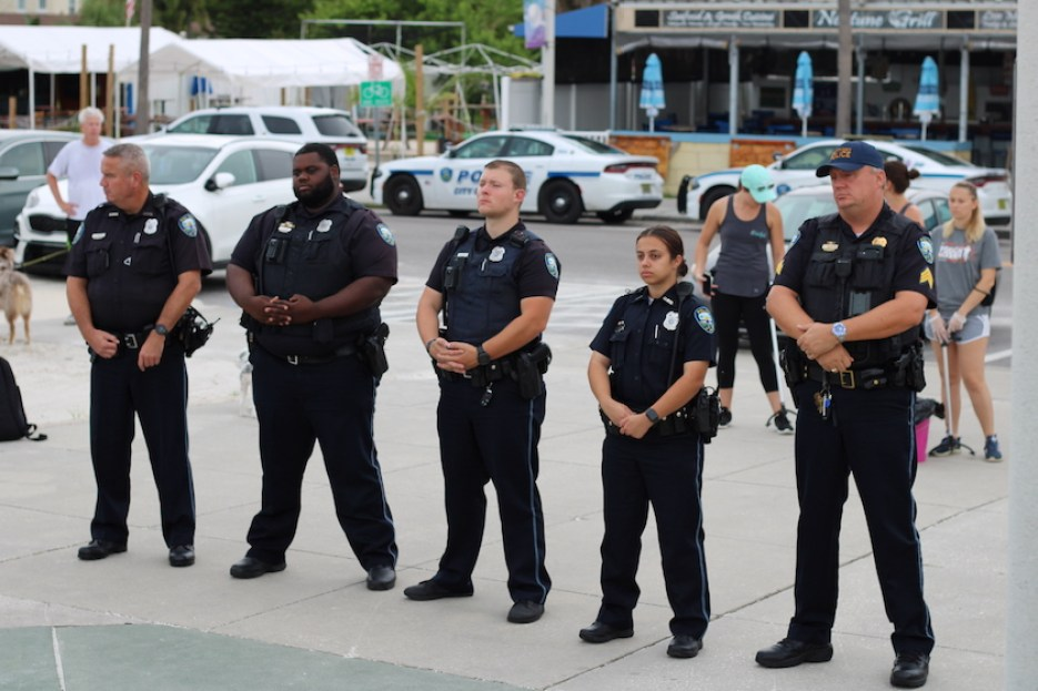 Five police officers in black uniforms standing in a row with police cars in the background.
