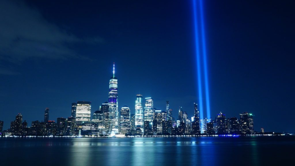 A photo of the skyline of New York City at night with two beams of light into the sky where the World Trade Center fell.