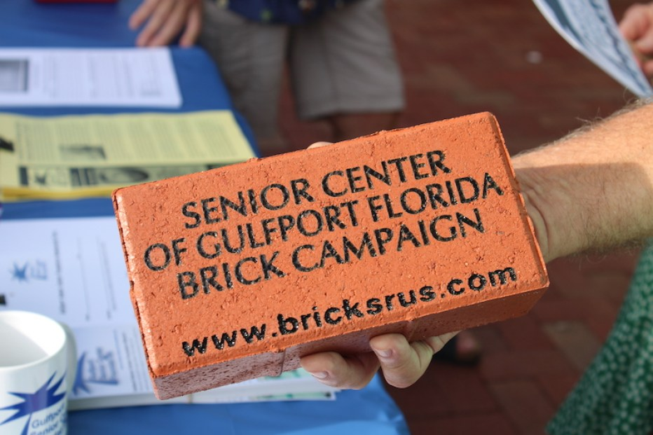 """A close up of a red brink with the words """"Senior Center of Gulfport Florida Brick Campaign www.bricksrus.com"""" engraved in black letters."""