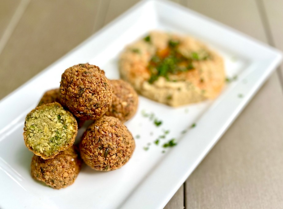 A photo of balls of falafel on a white plate with an orange sauce.
