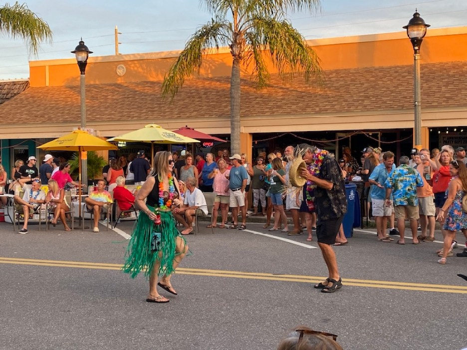 A photo of a woman in a hula costume dancing with a man on a street with a crowd behind them.
