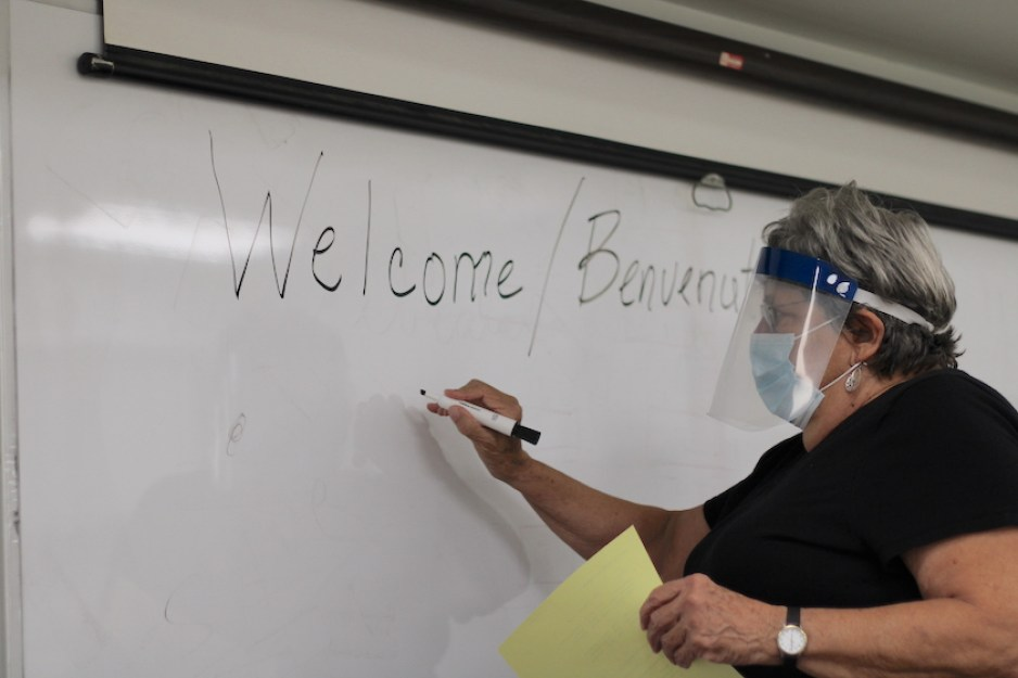 """A photo of a woman in a plastic face shield writing """"Welcome/Benvenuto"""" on a whiteboard with a marker."""