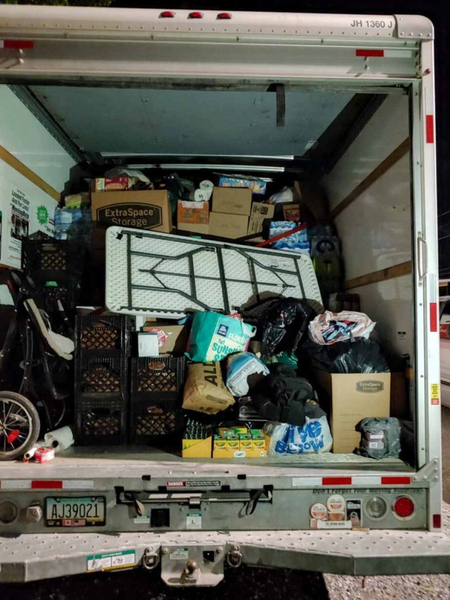 A photo of the back of a cargo truck packed full of supplies.