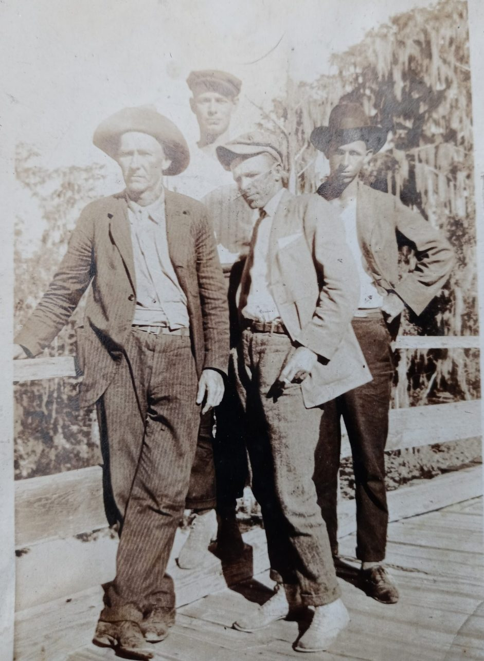 An old black and white photo of three men in working clothes and hats standing, looking at the camera.