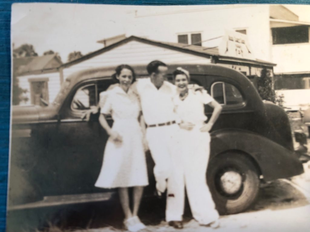 An old black and white photo of two men and a woman dressed in white standing in front of a black 1930s era car