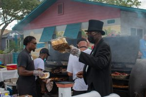 A photo of a man in top hat and tuxedo jacket standing by an outdoor BBQ holding a tray as people work in the background.