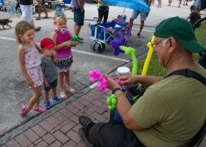 A photo of a man making balloon animals as three young children look on in the street.