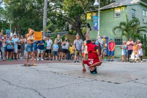 A photo of a street performer in a red shirt and shorts spinning on his head as a crowd of people look on.
