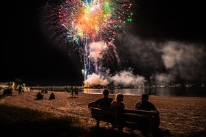 A night photo of people sitting on a beach bench watching fireworks above them.