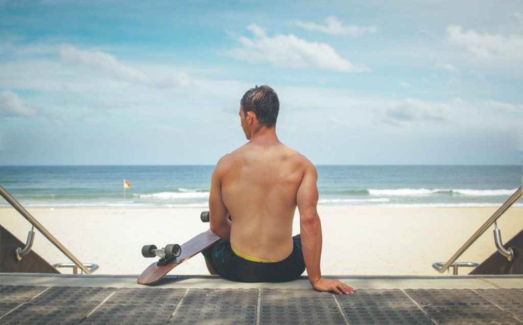 A photo of the back of a man with no shirt on sitting on steps with a skateboard looking at the water and the beach.