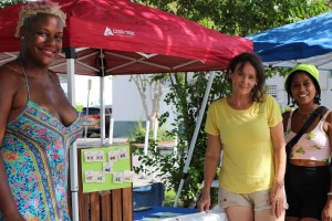 A photo of three women smiling at a camera outside of a red market stall tent.