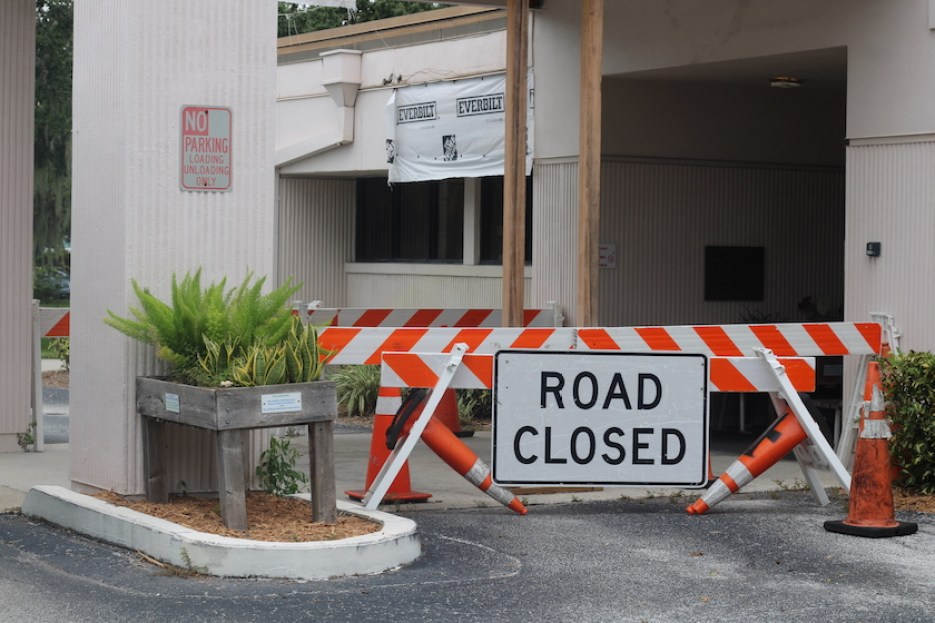"""A photo of the entrance to a building with an orange and white barricade that reads """"Road Closed"""""""