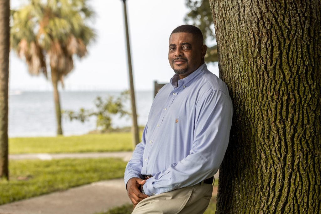 A photo of a man in a blue button-down shirt leaning against a tree with grass, water and a palm tree in the background.