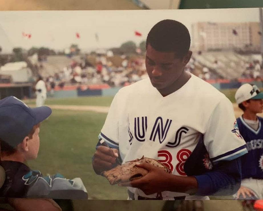 A photo of a man in a baseball uniform on a field signing an autograph for a child.