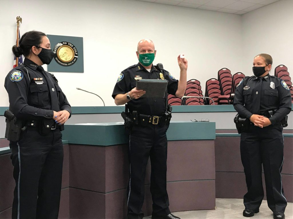 A man in a police uniform with a green mask and his hand raised in between two other police officers with masks in front of a podium.
