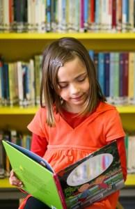 A little girl in an orange shirt reading a book