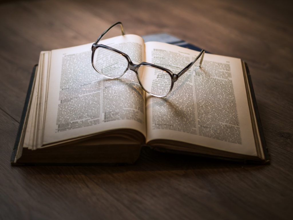 A pair of glasses on an old history book