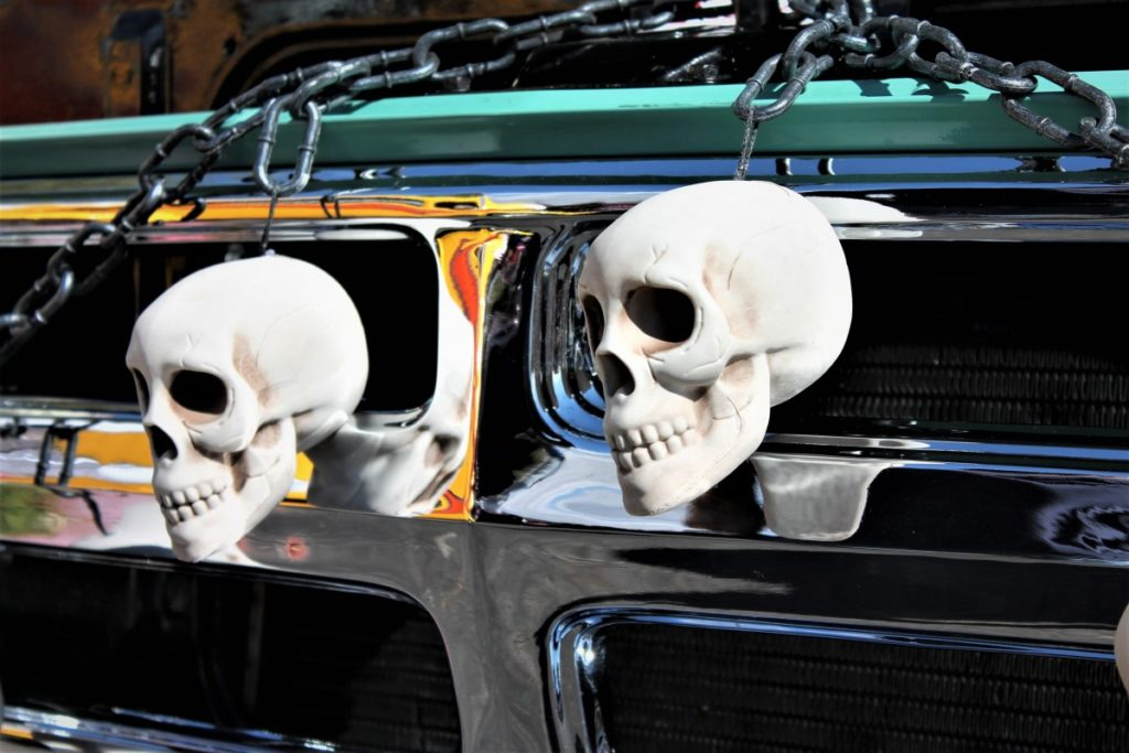 A photo of two white human skulls attacked to the grill of a car.