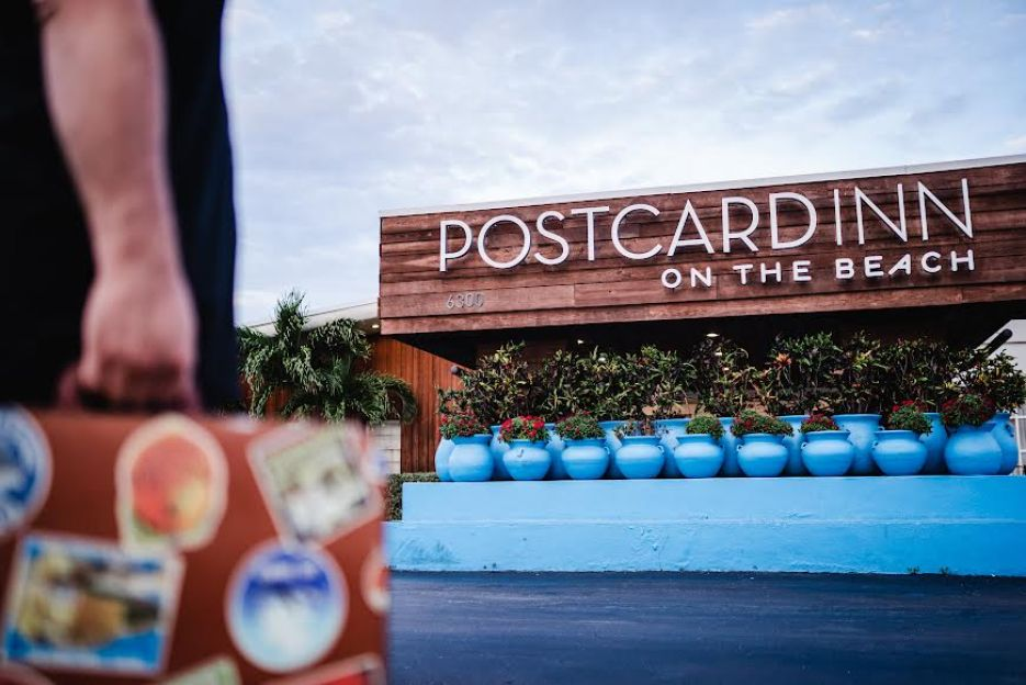"""A photo of a person walking with a suitcase and a hotel with a sign that reads """"Postcard Inn on the Beach"""" in the background."""