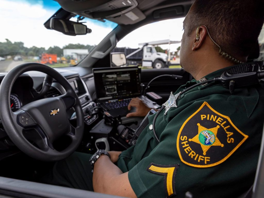 """A photo of a police officer in his cruiser in uniform with a patch that reads """"Pinellas Sheriff"""""""