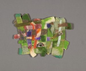 A piece of mainly green fiber art with some pinks reds and beige