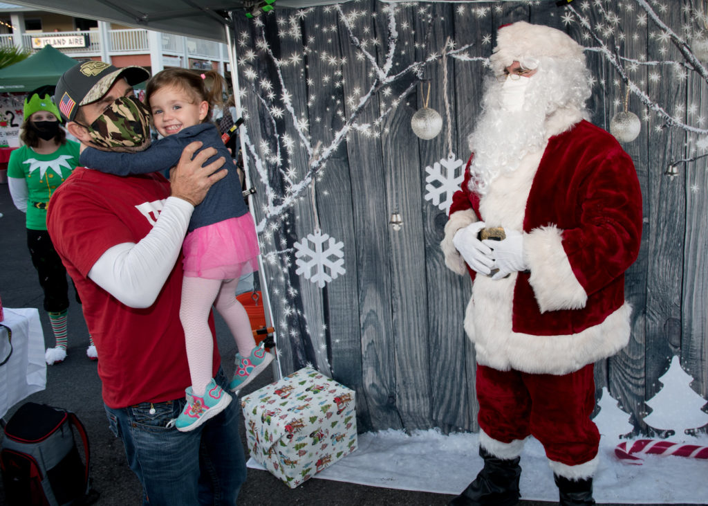 A photo of a Man holding a child next to a man dressed as Santa with a white, winter background.