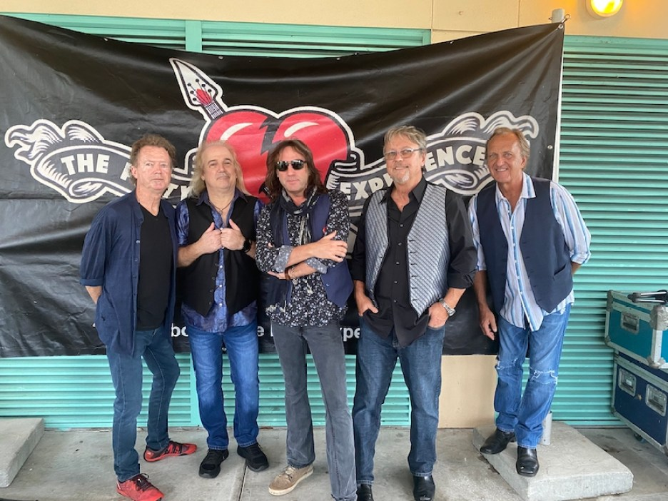 A photo of a five men in a band posing in front of a black banner with a red heart on it.
