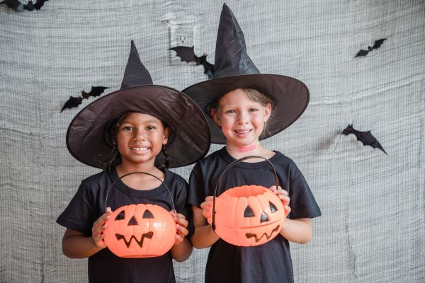 A little girl and a little boy holding orange pumpkins in black outfits and witch hats