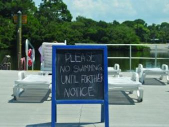 A sign posted at Eckerd College Tuesday warns students that it's still not safe to swim in Frenchman's Creek.