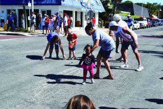 Adults and children pick up parade candy in the street.