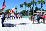 Members of the Boca Ciega High School JROTC Drill Team Color Guard, the greeting committee, right, and athletes, center, stand at attention while Elizabeth Brown-Worthington of Gulfport sings the national anthem during the opening ceremonies of the fifth annual VETSports Beach Volleyball Gulfport Open.