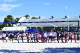 Volleyball players in a line serve balls over the net to officially kick off the fifth annual VETSports Beach Volleyball Gulfport Open.