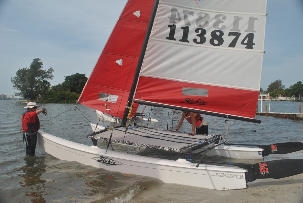 """Bob Johnson and Jennifer Ehrhart set up their Hobie catamaran for the Gulfport Yacht Club's Multi-Hull Regatta on Saturday April 30 in Boca Ciega Bay. """"It's a bouy race,"""" Johnson said. """"You go into the wind on the first leg and then come down wind. You're going back and forth and you finish where you start."""" According to fellow sailor Beth Langefeld, who has been racing for 15 years, the Hobie 16 is a """"quintessential"""" catamaran. """"It's a beach catamaran that pushes right off the beach,"""" Langefeld said. """"It's a lot of fun. Today, we'll get upwards of about 12 to 15 knots."""" Fifteen knots is equal to roughly 17 mph. Langefeld was the crew on her H16 class regatta. She and her skipper Jason Sanchez came in first place in their class."""