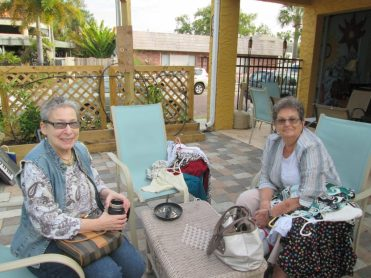 Sande Nelson and Jo Garland take a break in the shade from shopping at the Tuesday Fresh Market Clothing Swap.