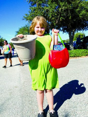 """Elizabeth McCaslin, 8, of Gulfport finds a book and a planter to upcycle from last Saturday's Junk in the Trunk event held last Saturday, October 24. """"I have basil seeds at home I am going to put in my new pot,"""" she said."""