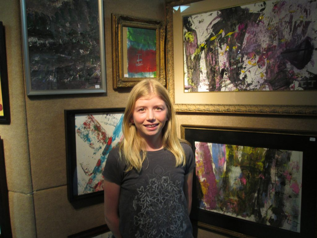 A girl stands in front of art at an exhibit