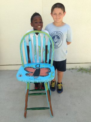 Xavier Murph, left, and Ayden Gross, show off their chair, which is illustrated with the stages of a monarch butterfly's development, a topic studied by the class. Photo courtesy of DonnaJo Reynolds.