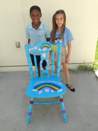 Syniya Jones, left, and Samantha Hoffmire with their rainbow-themed chair. Photo courtesy of DonnaJo Reynolds.