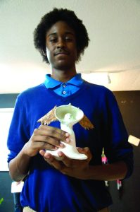 """Julion Burnett, 15, talks about his air-dried and oven-baked clay sculptures  at the City of Imagination's """"Celebration of Our Youth"""" art show and reception at the January 2 First Friday event. The event featured a handful of young artists with ties to Gulfport."""
