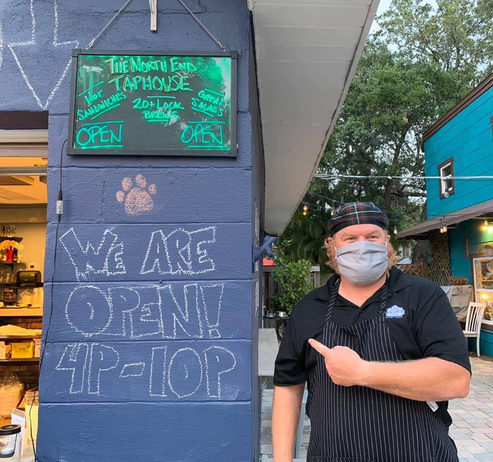 North End TapHouse worker in Gulfport wearing mask pointing to Open sign