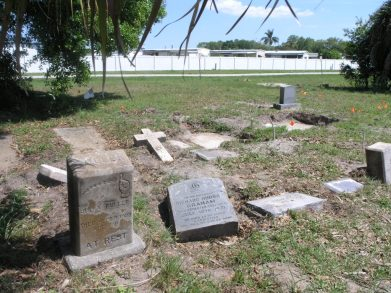 Holes in the ground above two graves, rear, with the Pinellas Trail in the background and orange flags placed at other unmarked graves.