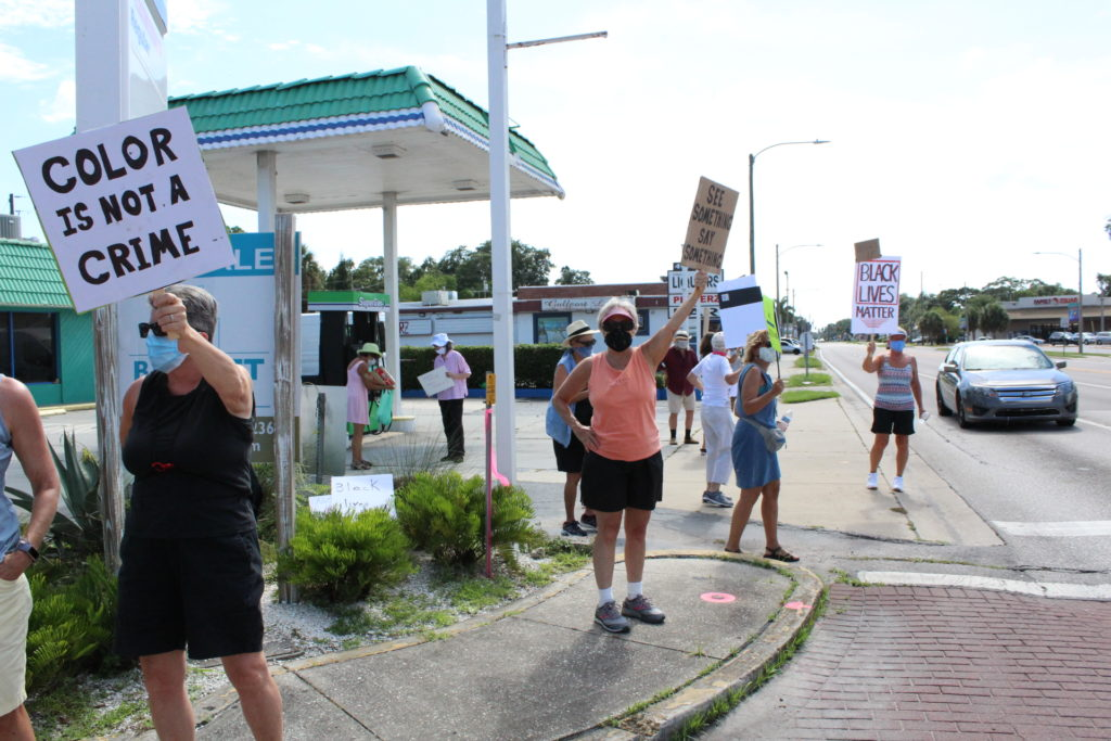 """A small group gathers at the corner of Gulfport Boulevard and 49th Street S. holding signs that read """"Color is Not a Crome"""" and """"Black Lives Matter."""""""