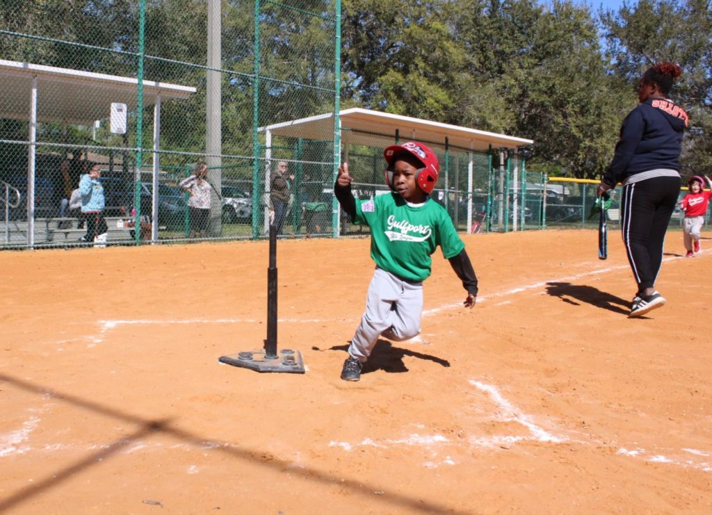 "A boy in a green baseball jersey that says ""Gulfport"" slides into home plate on a ballfields"