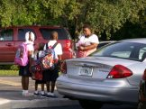 """Takia Wooten, right, takes pictures of her children, from left, Ta'Naya, 7, Elijah, 5, and Ja'Kari, 9, all with crisp uniforms and colorful backpacks, on the first day of class Monday at Gulfport Montessori Elementary School. Elijah, who was attending school for the first time, said he was excited about going to kindergarten """"because I want to go to school."""" The family lives in St. Petersburg."""