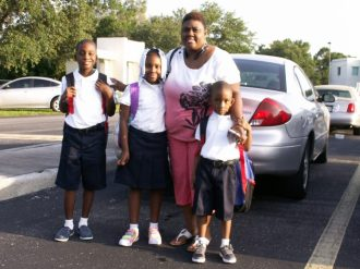 """Takia Wooten poses with her children, from left, Ja'Kari, 9, Ta'Naya, 7, and Elijah, 5, before heading into Gulfport Montessori Elementary School on Monday for the first day of class. The children all wore crisp uniforms and colorful backpacks. Elijah, who was attending school for the first time, said he was excited about going to kindergarten """"because I want to go to school."""" The family lives in St. Petersburg."""