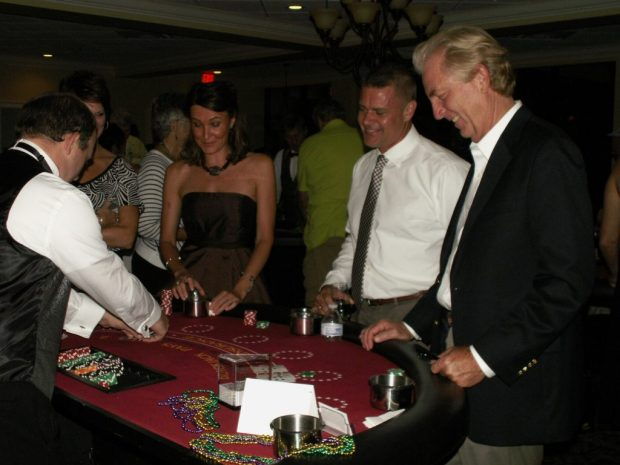 From right, Lee Hicks, general manager of Maximo Marina, and Kent Rodahaver, co-chair of the Skyway Marina District's marketing committee and an event organizer, join other guests at the 21 table during the fundraiser Saturday, September 26.