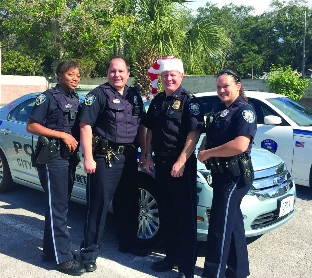 Four police officers in uniform stand in front of a car; one is wearing a Santa hat.