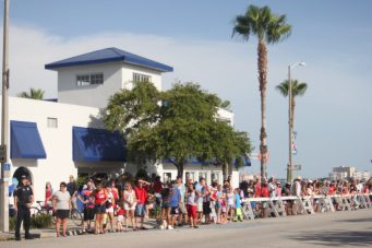 A crowd lines the street waiting for the parade to start.